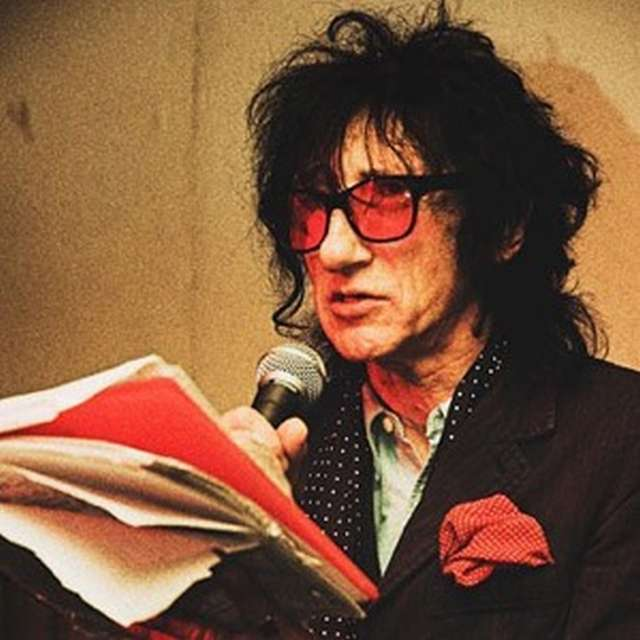John Cooper Clarke wearing rose lens glasses and speaking into a microphone